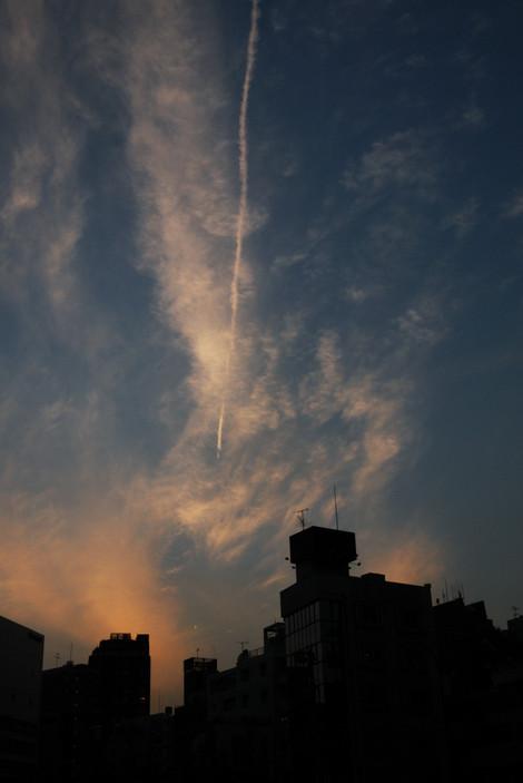 夕暮れの空に輝く飛行機雲